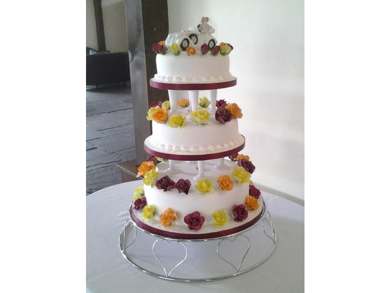 Flowers in claret, orange and yellow colourful wedding cake for pauline's special day at Great Hall of Mains